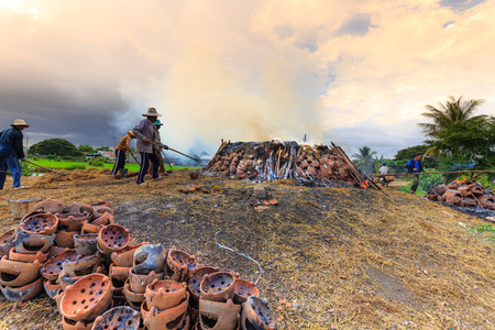 fling: Binh Thuan province, Vietnam - October 12, 2015 at Binh Duc traditional pottery village, the handicraftsmen burn products, ask for their m made by hands in the traditional way with wood and rice straw outdoors Editorial