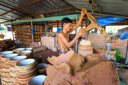 out of production: Binh Duong province, Vietnam - October 25, 2015: workers working in ceramics production base. They used clay to shape by hand out flower pots Editorial