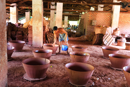 out of production: Binh Duong province, Vietnam - October 25, 2015: workers working in ceramics production base. They used clay shaped by hand out of flower pots chng Editorial