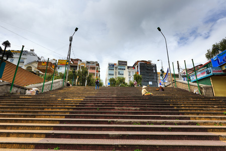 tense: Da Lat city, Vietnam - November 01, 2015: stairs going up the hill near the central city of Da Lat Market. These stairs built for an age past tense. Da lat is famous with its wine and fruit of kinds