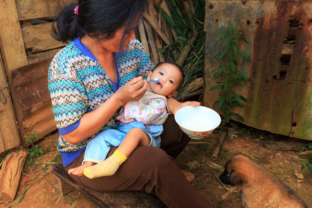 vietnamese ethnicity: Lam Dong Province, Vietnam - November 7, 2015: A view of daily life in the family from Minority ethnic highlands. The mother are feeding baby ngn