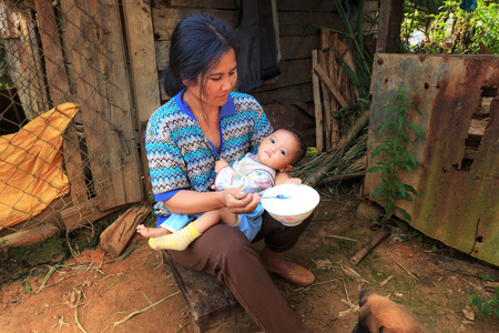 baby girls smiley face: Lam Dong Province, Vietnam - November 7, 2015: A view of daily life in the family from Minority ethnic highlands. The mother are feeding baby ngn