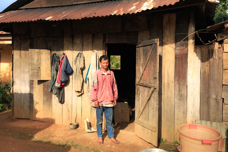 vietnamese ethnicity: Lam Dong Province, Vietnam - November 7, 2015: a man of ethnic Minority People in high mountainous areas to wooden house is Beside his Editorial