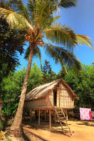 a house with a straw: bamboo stilt houses of ethnic Minority People in high mountain forests Stock Photo