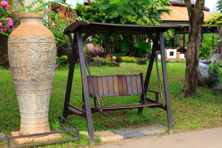 ornamental garden: outdoor wooden bench swing in the green park a large ceramic vase Beside