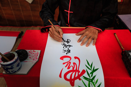 20 year old: HoChiMinh city, Vietnam - Jan 20, 2016 : A young Vietnamese scholar at lunar new year calligraphy festival organizing at HoChiMinh city. Calligraphy is old culture of Vietnam