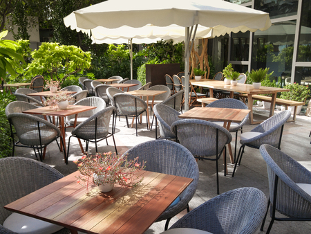 parasols: Chairs and tables of a restaurant seating outside with parasols.