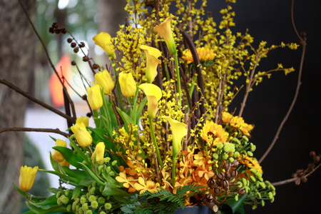 artisans: floral arrangement art basket with tulips, yellow daisies is made by artisans Stock Photo