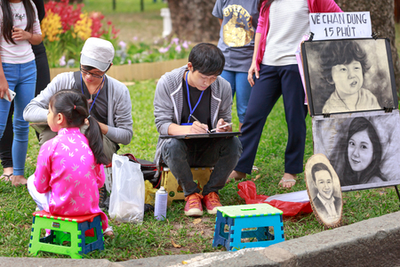 goodliness: Hochiminh City, Vietnam - February 4, 2016: Two young artist is painting portraying in Tao Dan Park in HoChiMinh city on the occasion of Lunar New Year 2016