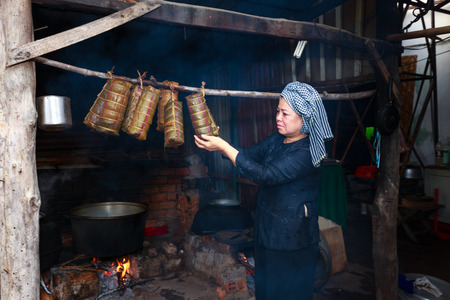 Hochiminh City, Vietnam - February 5, 2016: woman southern Vietnam is boiled tet cakes for the Lunar New Year. Tet cakes and chung cakes made from glutinous rice, meat, green beans, cover with banana leaves, and tie with bamboo string. They are Vietnamese Sajtókép