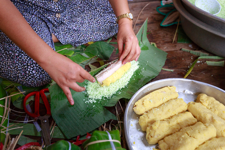 holiday food: Hochiminh City, Vietnam - February 5, 2016: woman southern Vietnam is package tet cakes for the Lunar New Year. Tet cakes and chung cakes made from glutinous rice, meat, green beans, cover with banana leaves, and tie with bamboo string. They are Vietnames