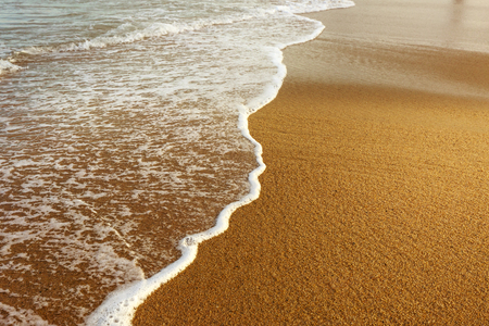 dangerously: Soft wave of the sea on the sandy beach Stock Photo