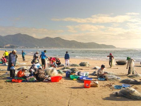 local supply: Nha Trang city, Vietnam - January 28, 2016 :  Women are selling fresh fishes at a local seafood market on beach in Nha Trang city