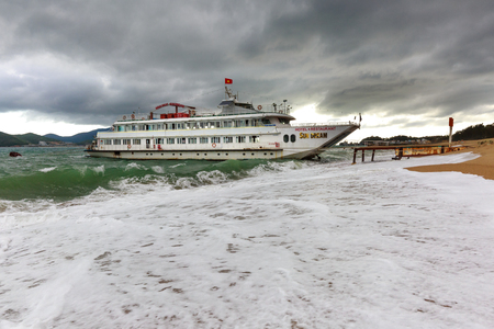 big waves: Nha Trang city, Vietnam - February 2, 2016: A tourist ship named Sun Dream parked near the shore with big waves and the sky full of dark clouds signal a big storm is coming at the NhaTrang beach, Vietnam Editorial