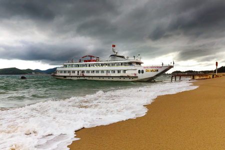 storm coming: Nha Trang city, Vietnam - February 2, 2016: A tourist ship named Sun Dream parked near the shore with big waves and the sky full of dark clouds signal a big storm is coming at the NhaTrang beach, Vietnam Editorial