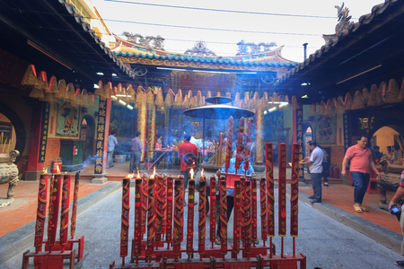 waft: HoChiMinh city, Vietnam - February 22, 2016: inside scene in a temple of Chinese at the HoChiMinh city with full huge incense sticks and cone incense burners, hooked from a ceiling of people who come here incense lit to pray for their family members to ha Editorial