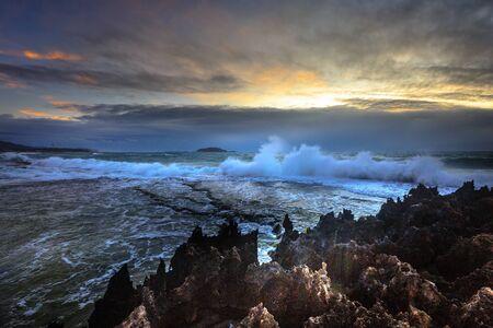 waves crashing: Amazing power of waves crashing Against the rocks at dawn Stock Photo