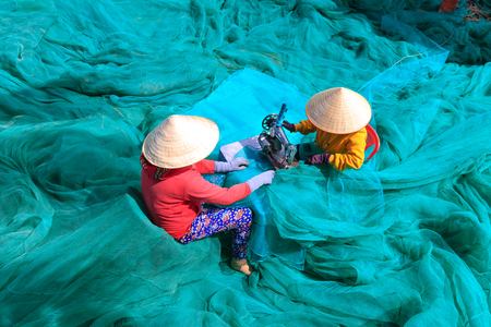 green life: Ninh Thuan Province, Vietnam - February 27, 2016: two women are sewing fishing nets in fishing village in Vinh Hy Bay, Phan Rang province. They work hard all day to sew large fishing nets