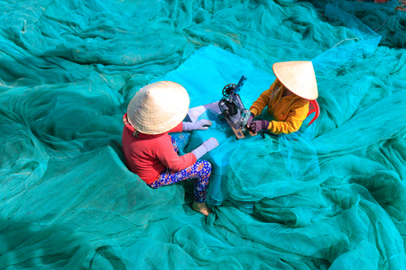 two women and one man: Ninh Thuan Province, Vietnam - February 27, 2016: two women are sewing fishing nets in fishing village in Vinh Hy Bay, Phan Rang province. They work hard all day to sew large fishing nets