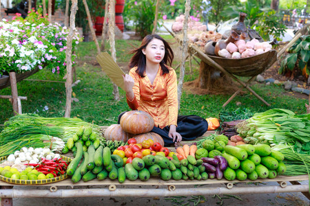salesgirl: Hochiminh City, Vietnam - March 5, 2016 : salesgirl with her bamboo basket full of vegetables in the culinary fair at the Van Thanh tourist area, Ho Chi Minh City which is modeled on the traditional market in the village Vietnam