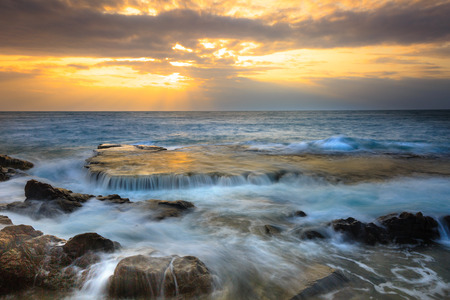 struck: At sunrise, many large waves struck the ancient coral rock coast at HangRai( Otter Cave) in the conservation area of the National Park mountain of God, creating a waterfall in the ocean. This is a famous tourist destination of Vietnam Stock Photo