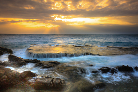 sunrise ocean: At sunrise, many large waves struck the ancient coral rock coast at HangRai( Otter Cave) in the conservation area of the National Park mountain of God, creating a waterfall in the ocean. This is a famous tourist destination of Vietnam Stock Photo