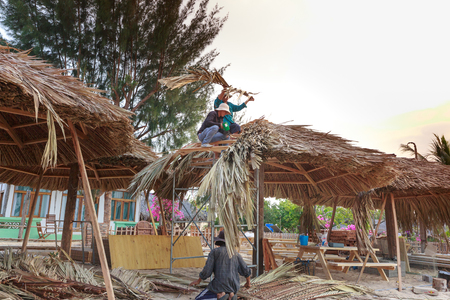 architecture bungalow: Lagi beach, Binh Thuan province, Vietnam - March 29, 2016: in a seaside resort, the builders are using dry coconut leaves roofing to complete the outdoor restaurant to serve tourists