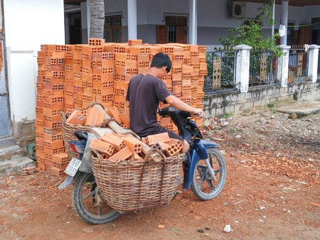 the emancipation: Ninh Thuan province, Vietnam - February 27, 2016: an unidentified man is trying to transport the bricks by motorcycle in rural Vietnam