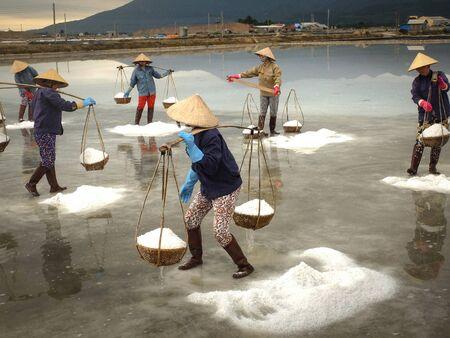 hon: Ninh Thuan Province, Vietnam - February 28, 2016 :the women are working on salt field at dawn. Salt field Hon Khoi in Nha Trang, Viet Nam. Workers transporting salt from the fields Hon Khoi, Viet Nam. Editorial