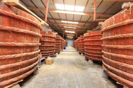 Phu Quoc eiland, provincie Kien Giang, Vietnam - 2 mei 2016: bij fabriek vissaus productie-installaties op Phu Quoc eiland door de traditionele gefermenteerde wijze van ansjovis gefermenteerde gebrouwen in grote houten vaten. naar de zuivere vissaus krijgen. dit produtio Stockfoto - 58570917
