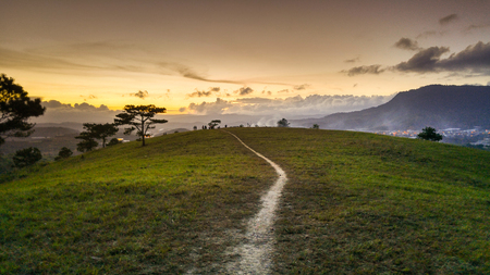 beautiful sunsets in a hilly area in Dalat, Vietnam. trails on hill  leading down to the valey bottom in sunset Stock Photo