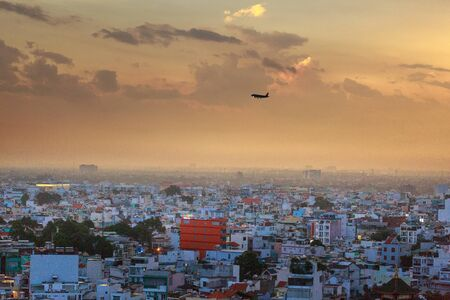 squatter: Ho Chi MInh City, Vietnam - July 15, 2016 :  airplane preparing to land down the airport. Impression landscape of Ho Chi Minh city at sunset