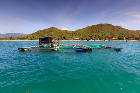 fish rearing: Cage aquaculture farming on sea of  fishermens at island Diep Son, Vietnam Stock Photo