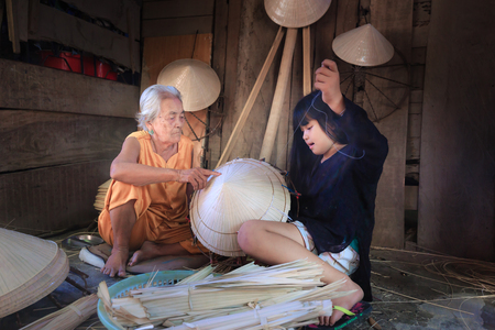 teaches: Nha Trang city, Viet Nam - July 31, 2016 : Old handicraft worker teaches her niece how to sew a Vietnamese traditional conical hat at a handicraft villages in Nha Trang city. conical hats are renown as womens hat in Vietnam Editorial