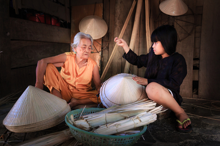 renown: Nha Trang city, Viet Nam - July 31, 2016 : Old handicraft worker teaches her niece how to sew a Vietnamese traditional conical hat at a handicraft villages in Nha Trang city. conical hats are renown as womens hat in Vietnam Editorial