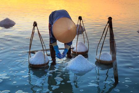 Hon Khoi, Khanh Hoa Province, Vietnam - July 30, 2016 : A woman is working on salt field at dawn. Salt field Hon Khoi in Nha Trang, Viet Nam. Workers transporting salt from the fields Hon Khoi, Viet Nam. Editorial
