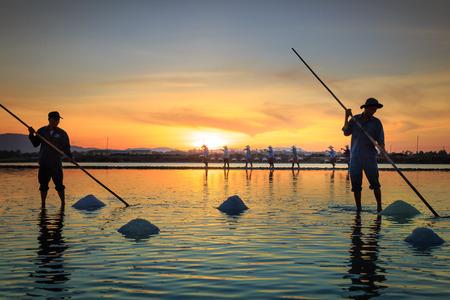 Hon Khoi, Khanh Hoa Province, Vietnam - July 30, 2016 :the men are working on salt field at dawn. Salt field Hon Khoi in Nha Trang, Viet Nam