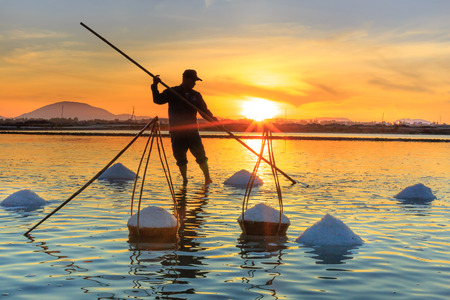 Hon Khoi, Khanh Hoa Province, Vietnam - July 30, 2016 :A man are working on salt field at dawn. Salt field Hon Khoi in Nha Trang, Viet Nam Editorial