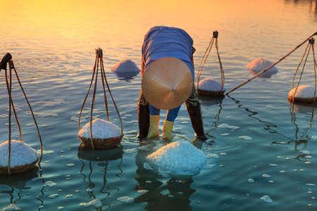 emerging markets: Hon Khoi, Khanh Hoa Province, Vietnam - July 30, 2016 : A woman is working on salt field at dawn. Salt field Hon Khoi in Nha Trang, Viet Nam. Workers transporting salt from the fields Hon Khoi, Viet Nam. Editorial