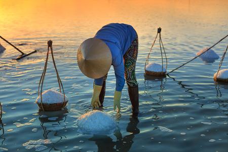 hon: Hon Khoi, Khanh Hoa Province, Vietnam - July 30, 2016 : A woman is working on salt field at dawn. Salt field Hon Khoi in Nha Trang, Viet Nam. Workers transporting salt from the fields Hon Khoi, Viet Nam. Editorial