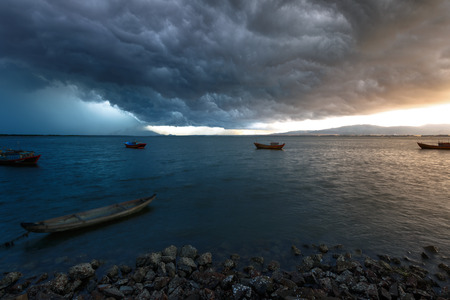 The sea during the storm is comming. Sea in a bad weather. Small boats and a dark clouds. Stock Photo