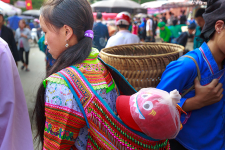 vietnamese ethnicity: Hoang Su Phi, Ha Giang Province, Vietnam October 2, 2016 :  picture of ethnic minority woman carrying a small child on her back at the sunday village fair in Hoang Su Phi, Ha Giang province, Vietnam