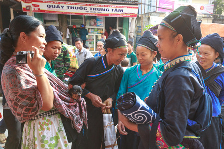 amigas conversando: Hoang Su Phi, Ha Giang province, Vietnam - October 2, 2016 : a friendly conversation between a traveler with her pet chihuahua dog and ethnic minority people at the sunday village fair in Hoang Su Phi, Ha Giang, Vietnam Editorial