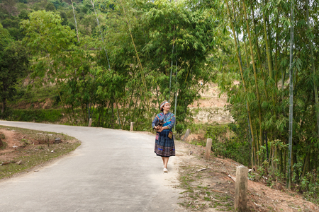 Hoang Su Phi, Ha Giang province, Vietnam - October 1, 2016 :  The Hmong ethnic woman happily walking on village road at Hoang Su Phi, Ha Giang Province