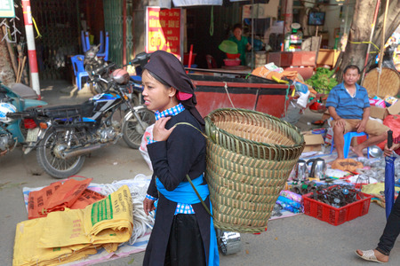 2 way: Hoang Su Phi, Ha Giang Province, Viet Nam October 2, 2016: The ethnic woman is wearing bamboo basket on the way to the village market in early morning.