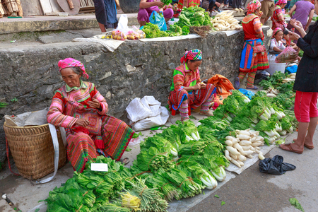 Hoang Su Phi, Ha Giang province, Vietnam - October 2, 2016: ethnic minority people set out the agricultural products plant by themselves at the Sunday fair in Hoang Su Phi. They sell the bundles of vegetables, fruits