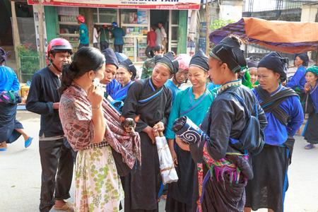 amigas conversando: Hoang Su Phi, Ha Giang province, Vietnam - October 2, 2016 : a friendly conversation between a traveler and her pet chihuahua dog with ethnic minority people at the sunday village fair in Hoang Su Phi, Ha Giang, Vietnam Editorial
