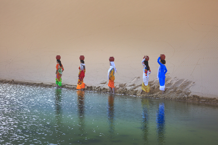 Phan Rang town, Ninh Thuan province, Vietnam - November 26, 2016 : the ethnic Cham women collecting water in the small lake in the middle of the sand dunes, they had to overcome dunes with water jars on their heads. This is their daily work