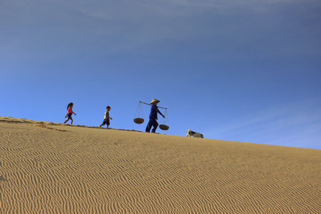 Phan Rang town, Ninh Thuan province, Vietnam - November 26, 2016 : woman carries a bamboo frame on the shoulder and two children walking home across the Mui Dinh sand dunes Ninh Thuan Province, Vietnam