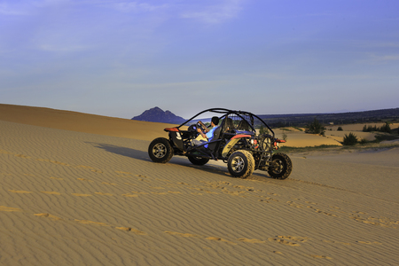 motorizado: Phan Rang town, Ninh Thuan province, Vietnam - November 26, 2016 : A group of tourists prepared to explore the sand dunes at Mui Dinh the seaside, Binh Thuan Province by coach terrain vehicles Editorial